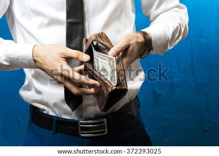 Man holding open wallet with money - stock photo
