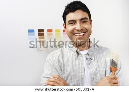 Man holding paintbrush, portrait - stock photo