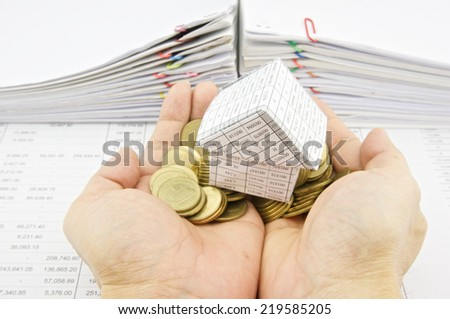 Man holding paper house on pile gold coins over finance account with pile of paperwork as background.