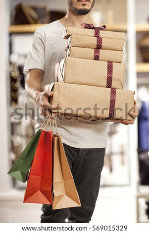Man holding paper shopping bag with gift boxes