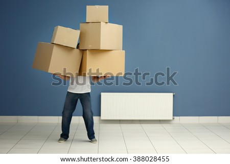 Man holding pile of carton boxes against blue wall in the room