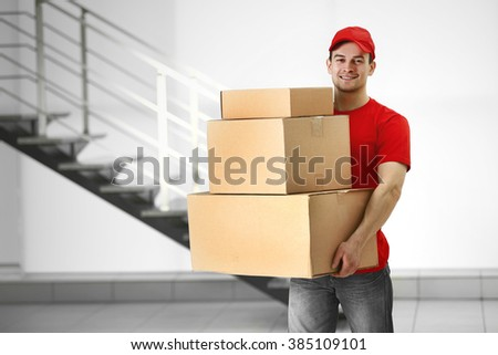 Man holding pile of carton boxes in the room - stock photo