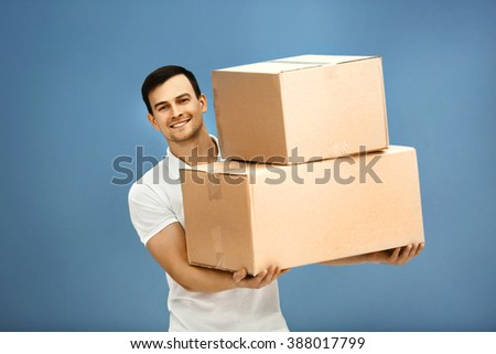 Man holding pile of carton boxes on blue background, close up - stock photo