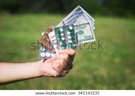 man holding pills and money, over natural background