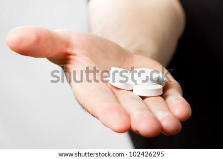man holding pills in hand - stock photo