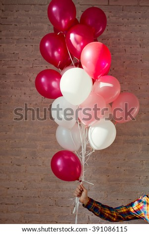 man holding pink and white baloons