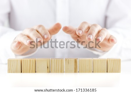 Man holding protective hands above a line of eight blank wooden cubes as he safeguards and protects them. Ready for your text. - stock photo