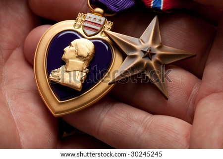 Man Holding Purple Heart and Bronze War Medals in The Palm of His Hand. - stock photo