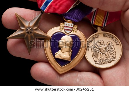 Man Holding Purple Heart, Bronze and National Defense War Medals in The Palm of His Hand. - stock photo
