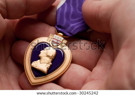 Man Holding Purple Heart War Medal in The Palm of His Hand. - stock photo