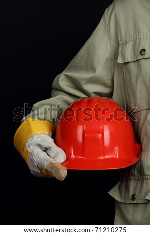 man holding red helmet over black background - stock photo