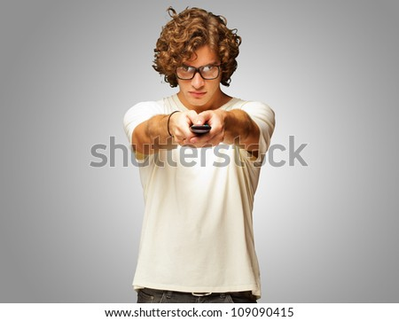 Man Holding Remote Control Isolated On Grey Background