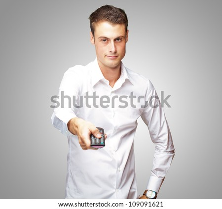Man Holding Remote In His Hand On Gray Background - stock photo