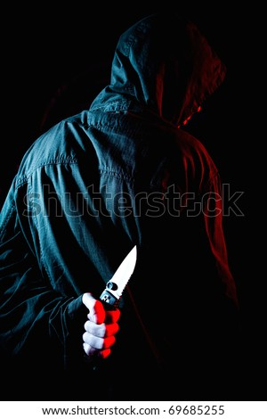Man holding sharp knife in a dark atmosphere, danger concept - stock photo