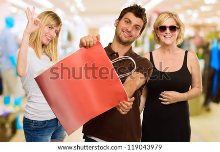 Man Holding Shopping Bag In Front Of Two Happy Women, Indoor - stock photo