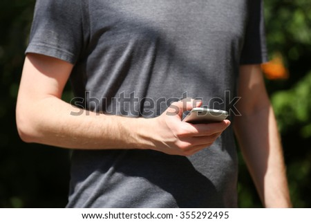 Man holding smart mobile phone outdoors