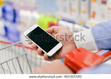 Man holding smart phone and reading text message during shopping, closeup - stock photo