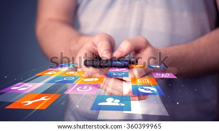 Man holding smart phone with colorful application icons comming out - stock photo