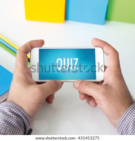 Man holding smartphone which displaying Quiz - stock photo