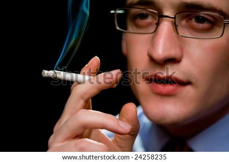 Man holding smoking cigarette over black - stock photo