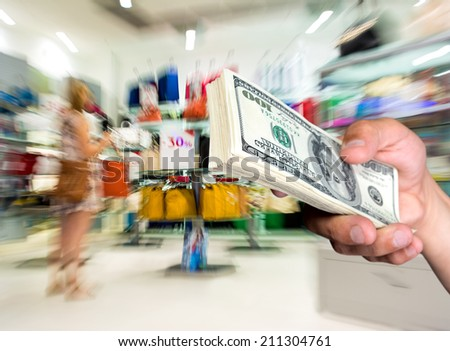 Man holding stack of dollar bills at shopping mall - stock photo