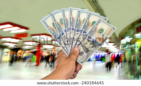 Man holding stack of dollar bills in the shopping mall - stock photo