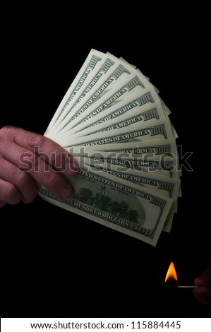 man holding stack of dollars and match fire - stock photo