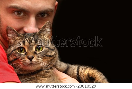 Man holding tabby cat with big green eyes - stock photo