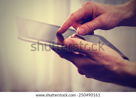 man holding tablet in the air while touching the screen with fingertip with a strong sun with a retro instagram filter (shallow depth of field) - stock photo
