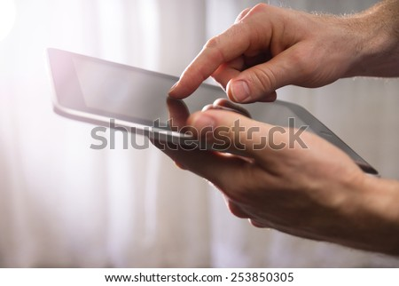 man holding tablet in the air while touching the screen with fingertip with a strong sun with a drama filter (shallow depth of field)