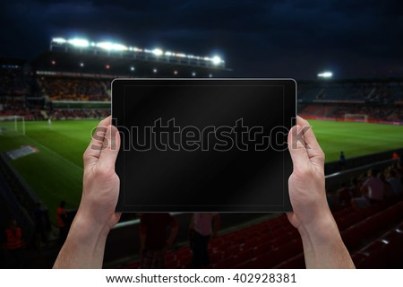 Man holding tablet with blank screen on soccer game. Stadium in background. - stock photo