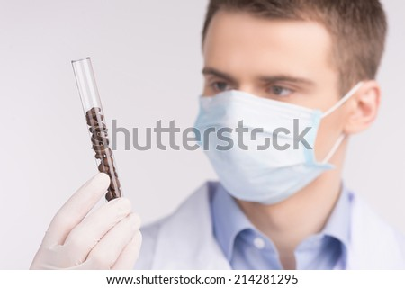man holding test tube and wearing mask. Cell culture assay to test genetically modified products