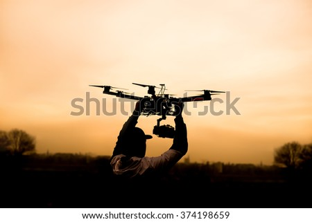 Man holding the drone, preparing for take off. Silhouette against the sunset sky. - stock photo