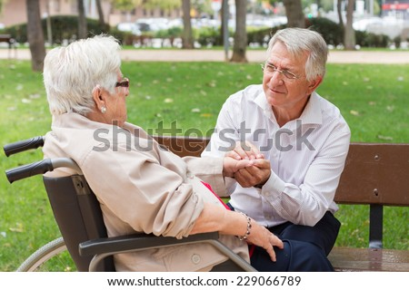 Man holding the hand of a senior woman in wheel chair talking at the park - stock photo