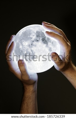 Man holding the Moon in his hands. Moon image provided by NASA. - stock photo