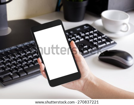 Man holding the phone over a workspace table - stock photo
