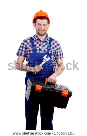 Man holding toolbox and wrench wearing overalls and helmet - stock photo