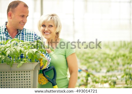 Man holding tray of plants with smiling woman looking at camera