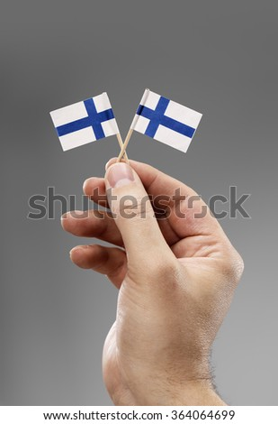 Man holding two small flags of Finland in his hand. - stock photo