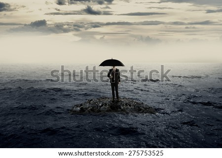 Man holding umbrella standing on the rock on the sea with bad weather. Business recession concept - stock photo