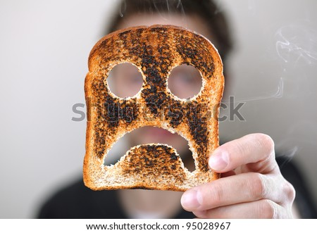 Man holding up a burnt slice of toast with an unhappy smiley concept for bad start to the day