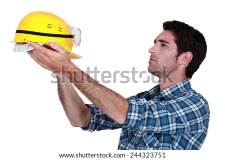 Man holding up a construction helmet - stock photo