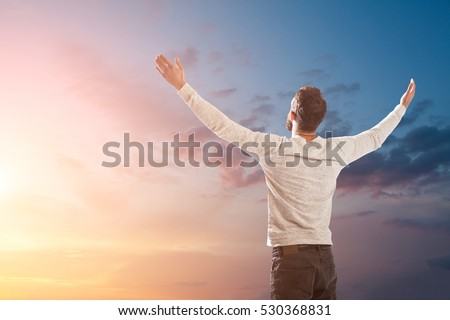 man holding up hands in order to praise God