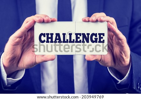 Man holding up two interlocked puzzle pieces with the word - Challenge - on them as he shows that there is a solution and answer and a way to success, toned retro or instagram effect. - stock photo