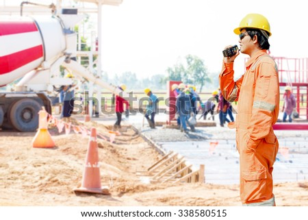 man holding walkie-talkie radio in hand, communication in construction site - stock photo