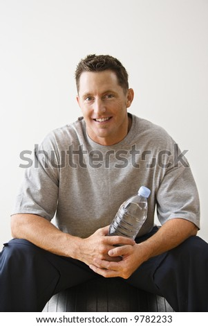 Man holding water bottle sitting on balance ball at gym smiling. - stock photo