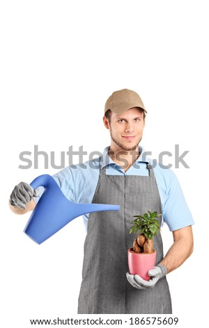 Man holding watering can and a plant isolated on white background - stock photo