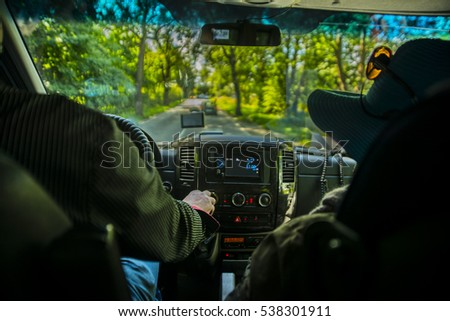 man holding wheel and transmission. mobile phone with gps in car, bus or public transport with screen computer. no face of  person. male sitting behind glass with woman. Couple inside bus or truck
