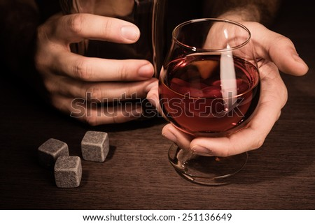 Man holding whiskey glass in hands - stock photo