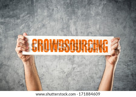 Man holding white banner with CROWDSOURCING title - stock photo